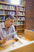 Professor holding digital tablet and reading book - stock photo