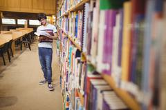 Young student reading book while standing near bookshelf - stock photo