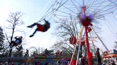 People on smaller chain carousel turn around in funfair Stock Footage