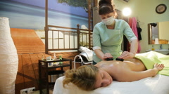 Woman in spa salon with hot stones Stock Footage