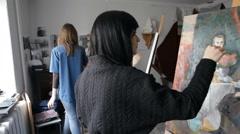 Artist brunette girl draws on easel Stock Footage