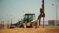Tractor with a drilling device at a construction site - stock footage
