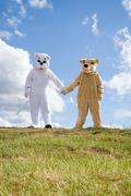 People in cat and dog costumes holding hands Stock Photos