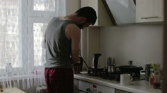 A man in a sleeveless shirt making coffee - stock footage