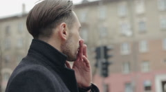 Handsome stylish young man smoking outside in urban setting, looking away Stock Footage
