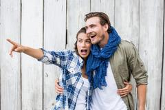 Young woman standing with man pointing upward - stock photo
