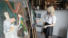blonde painter draws paints on an easel - stock footage