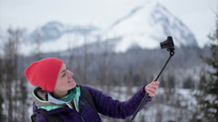 Tourist girl making selfie photo with stick in winter scenery HD Stock Footage