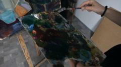 Girl artist paints on an easel painting in a studio Stock Footage