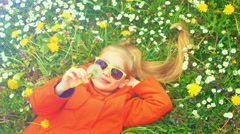 Closeup portrait of a child. Girl holding a dandelion and laughing at the camera Stock Footage