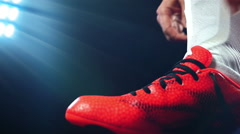Football, soccer game. Professional footballer buckle his red shoes, slow motion Stock Footage