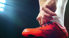 Football, soccer game. Professional footballer buckle his red shoes - stock footage