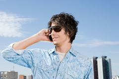 Young man using a cellular telephone - stock photo