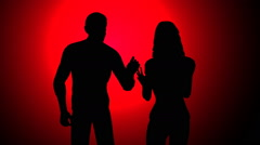 Woman and man in silhouette arguing on a red background - stock footage