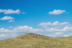 Timelapse prairie hill side with blue sky and clouds Stock Footage