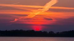 Beautiful sunset over lake, sun hiding under horizon - stock footage