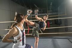 women boxer practicing body combat attack. - stock photo