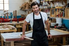 Carpenter is posing with his craft - stock photo