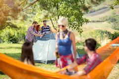 Youth in woods set up tent - stock photo