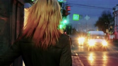 Young blond haired woman in nights street looking back toned shot Stock Footage