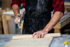 Carpenter working on his craft - stock photo