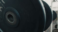 Athlete bodybuilder puts weight on the barbell Stock Footage