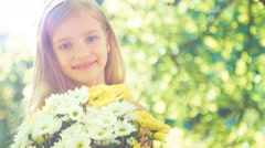 Closeup portrait girl holding bouquet of flowers and showing flowers at camera Stock Footage