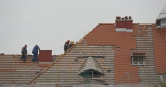 Workers in Safety Helmets Repair a Roof Tiles Placed on Wooden Frame on the Stock Footage