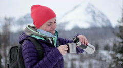 Young woman pouring and drinking tea from a thermos cup in the mountains HD Stock Footage
