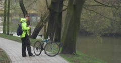 Man is Riding a Bicycle in Park Alley Backpacker Near the River Water Flows Stock Footage
