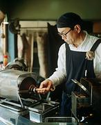 Man roasting coffee beans - stock photo
