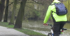 Man is Riding a Bicycle Stops Gets Off in Park Alley Backpacker in Glasses is Stock Footage