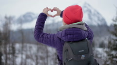 Woman holding hands in heart shape against beautiful view in the mountains HD Stock Footage