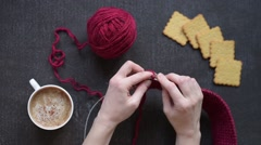 Woman knitting while drinking coffee Stock Footage