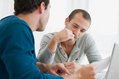 Gay couple doing finances Stock Photos