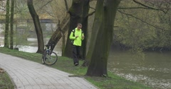 Man Scrolls a Tablet Near Bicycle in Park Tourist is Riding a Bicycle Sits to a Stock Footage