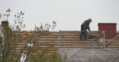 Worker in Orange Helmet Repairs Roof of Building Leans Down Installing Red Stock Footage