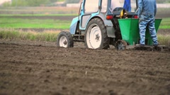 Agricultural tractor plows soil and plantings of agricultural cultures, blurred - stock footage