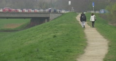 Couple is Walking Away by Footpath to the Bridge Landscape Green Lawn Cityscape Stock Footage