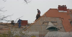 Workers in Helmets Repair a Roof Walking on Top of Building Red Tiles on the Stock Footage