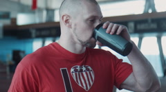 The tired athlete drinks water - stock footage