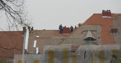 Roofers Repair a Roof of Building Red Tiles Placed on Base of Wooden Logs on Stock Footage