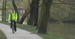 Man is Riding a Bicycle in Park Alley Backpacker Near the River Water Flows - stock footage