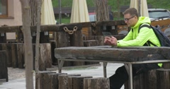 Tourist is Talking Holding Tablet Makes Call Cafe Outdoors Talking Via Stock Footage