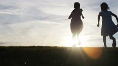 4K Silhouette children running towards the sunset, in slow motion Stock Footage