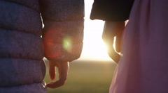 4K Two young children hold hands as they watch the sunset, in slow motion Stock Footage