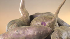 Sweet Potatoes isolated rotating on brown background Stock Footage