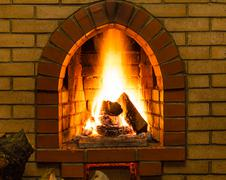 Spurts of fire in brick fireplace Stock Photos