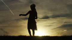 4K Silhouette of young child playing with bubbles at sunset, in slow motion Stock Footage