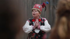 Old lady in a traditional Slavic clothing explaining customs and rituals Stock Footage